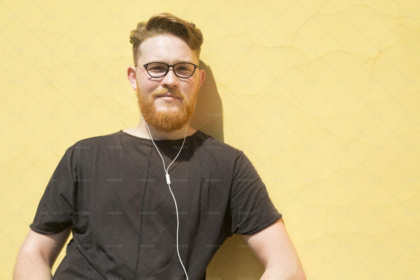 A Bearded Man Listens To Music: Stock Photos