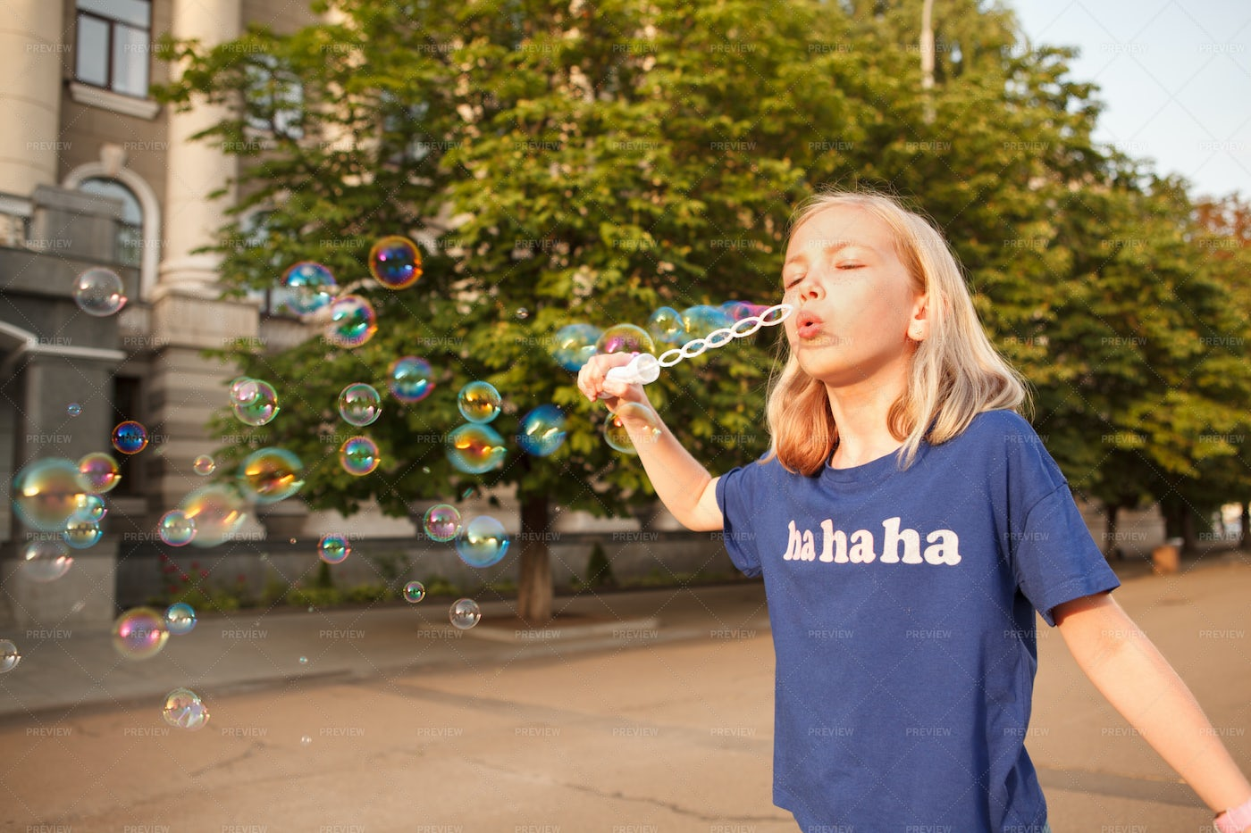 Young Girl Blowing Bubbles Outdoors: Stock Photos