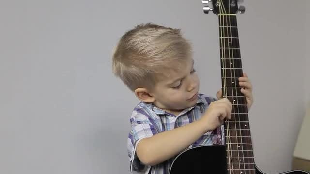 Little Boy Plays With Guitar: Stock Video