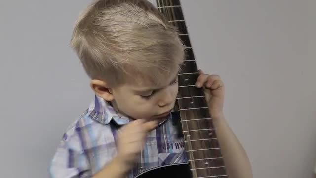 Little Boy Plays a Guitar: Stock Video