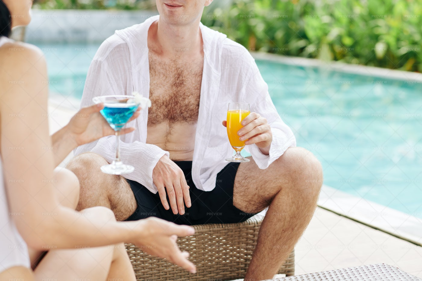 Couple Sitting By Swimming Pool: Stock Photos