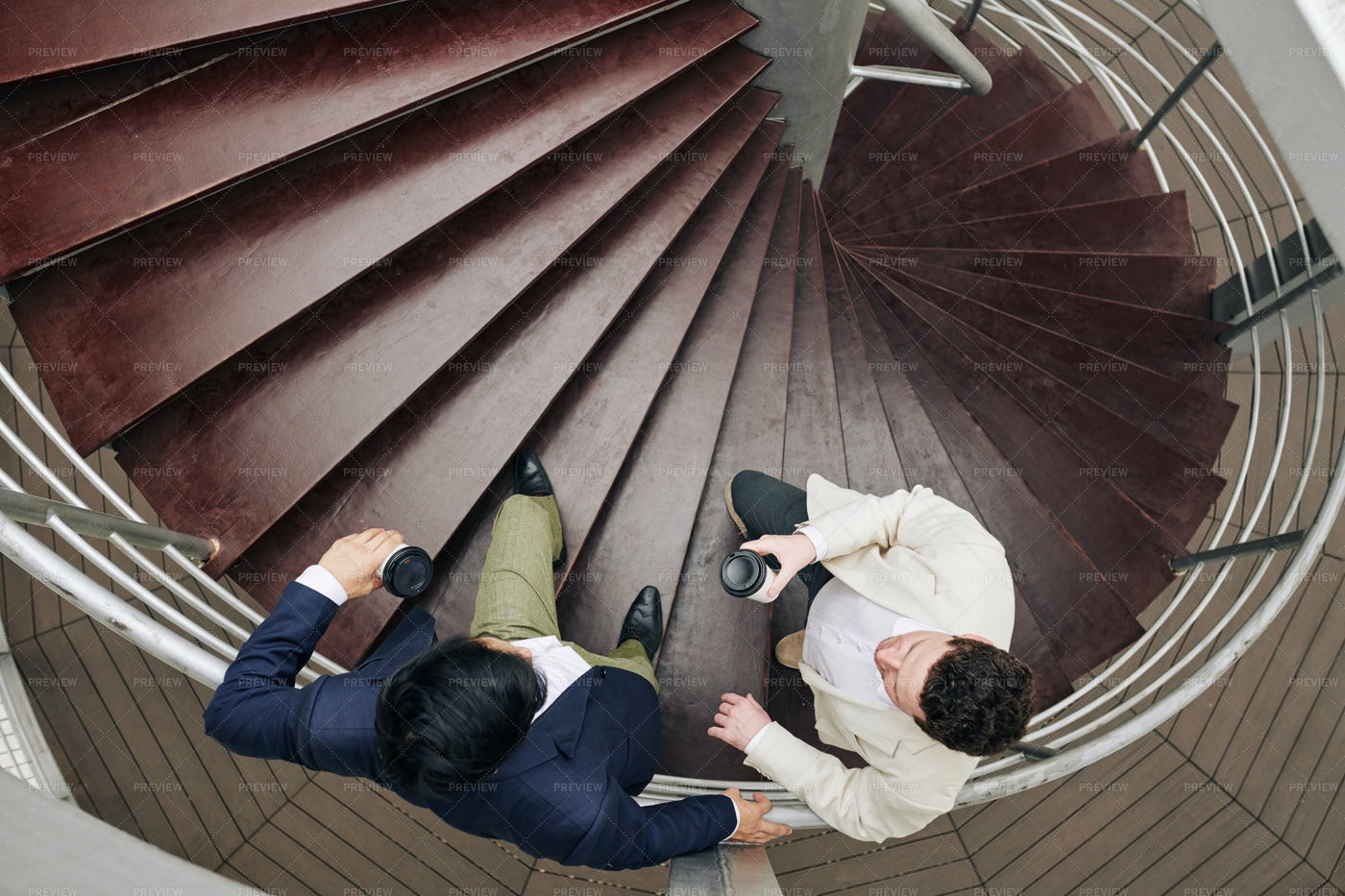 Coworkers Talking On Spiral Staircase: Stock Photos