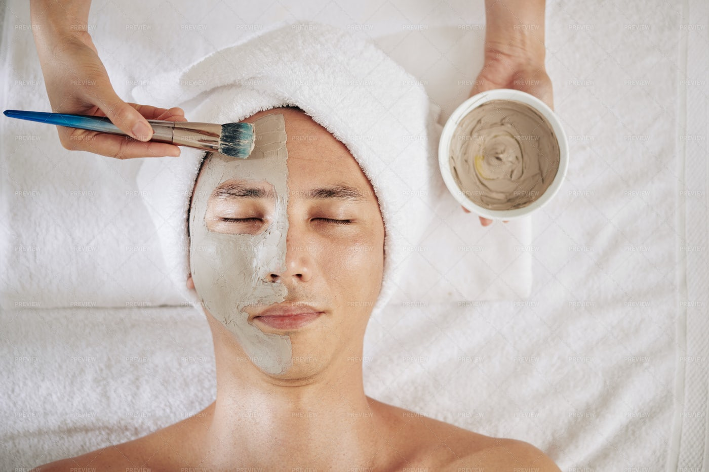 Cosmetologist Applying Charcoal Mask: Stock Photos