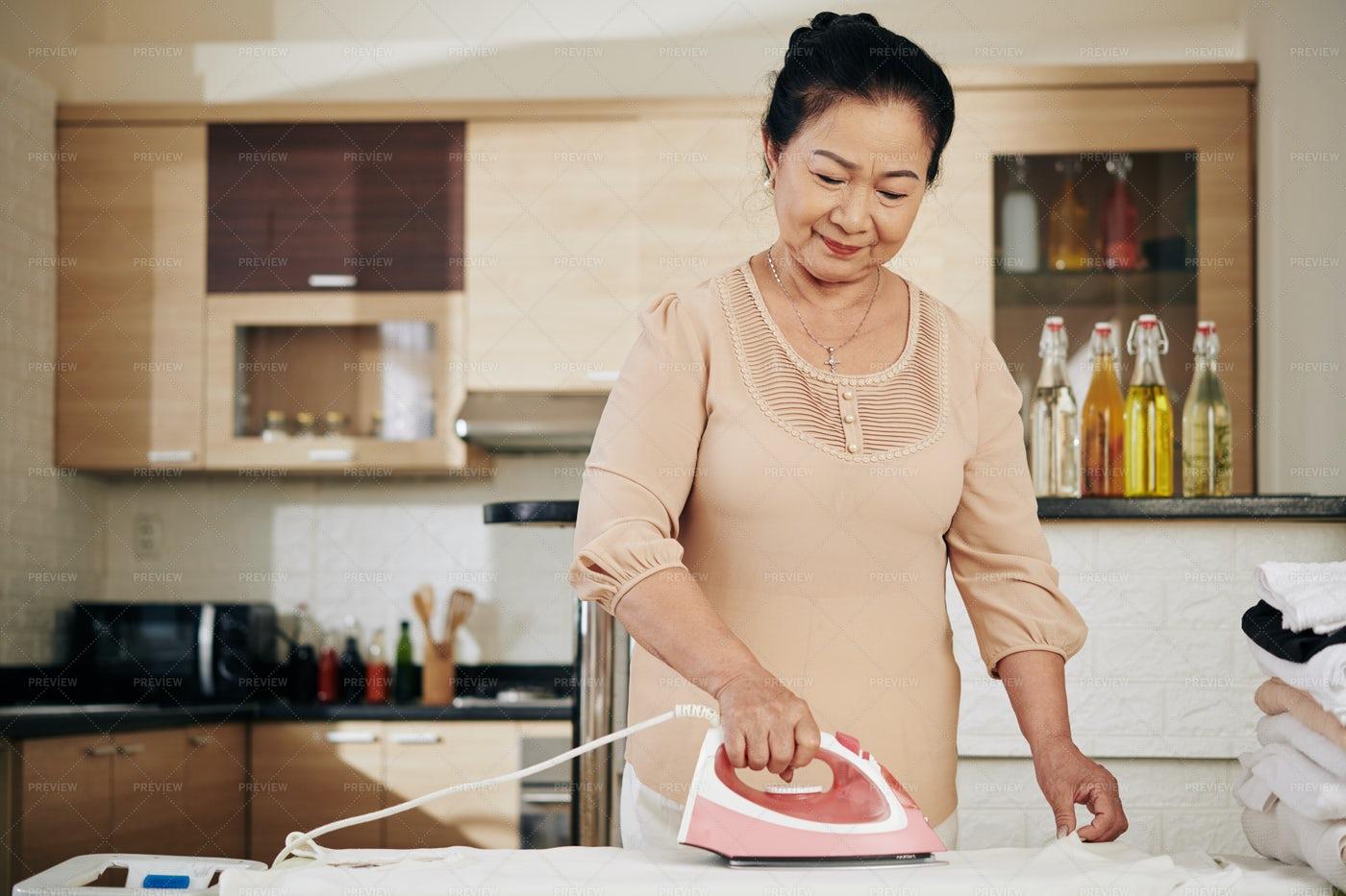 Senior Woman Ironing Clothes: Stock Photos