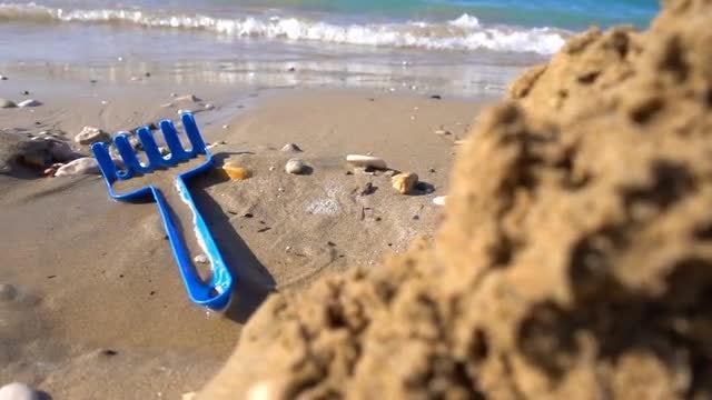 Toy Rake On The Beach: Stock Video