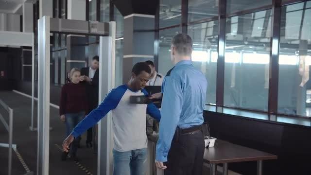 Airport Security Guard Flisking Passengers: Stock Video
