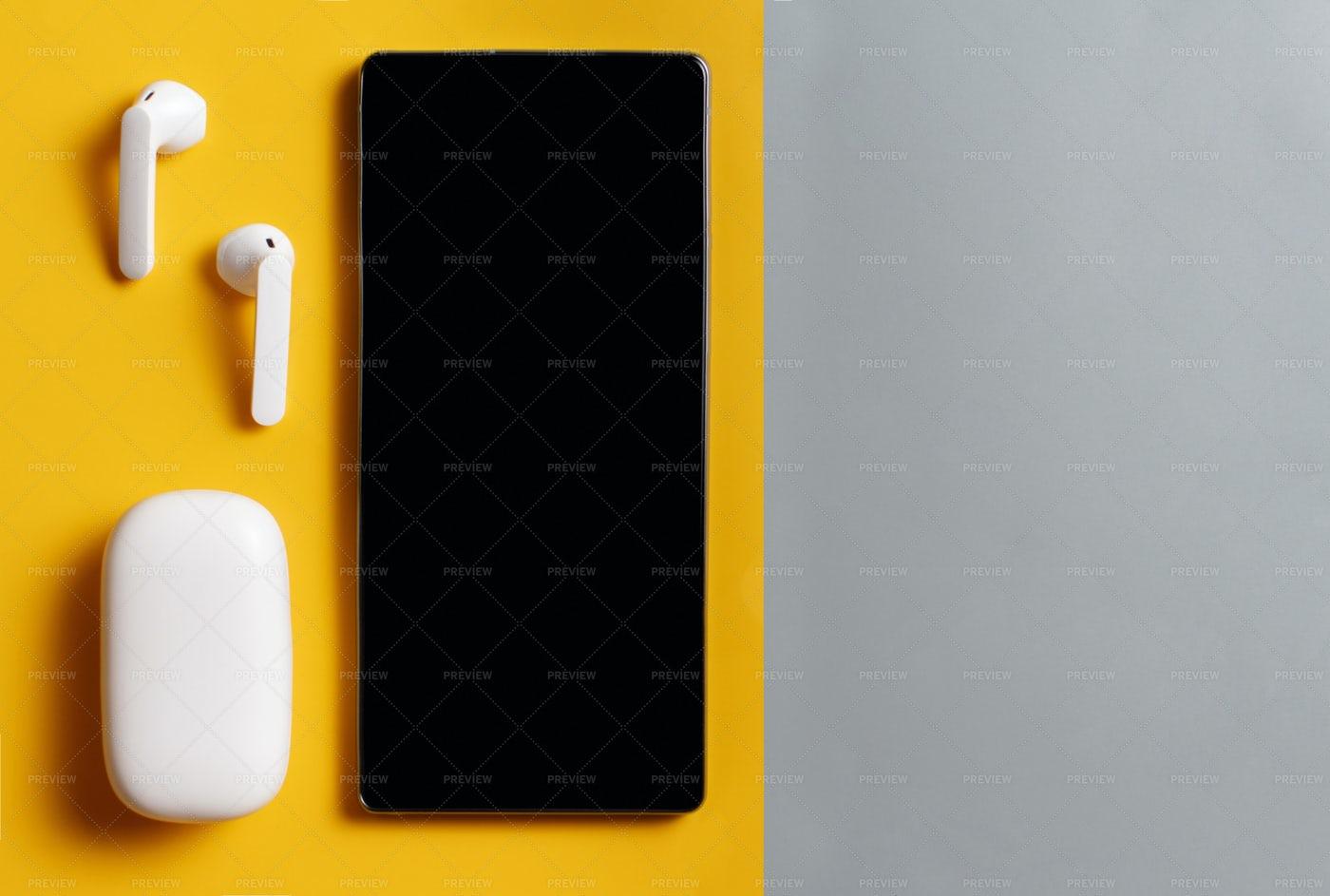 Wireless Earphones And Phone: Stock Photos