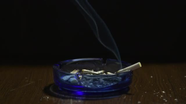 Burning Cigarette On Glass Ashtray: Stock Video