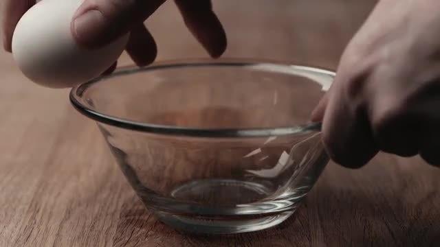 Cracking An Egg Into Bowl: Stock Video