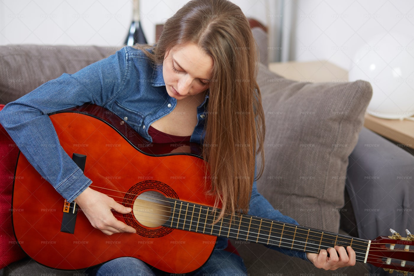 Playing Guitar On The Couch: Stock Photos
