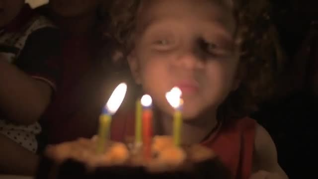 Child Blowing Out Candles: Stock Video