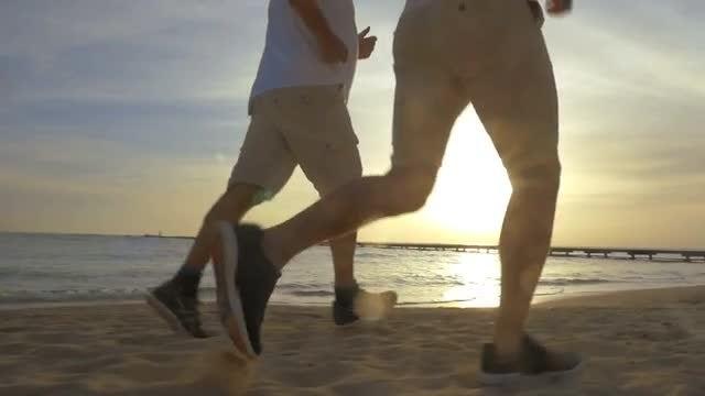 Two Men Jog On Beach: Stock Video