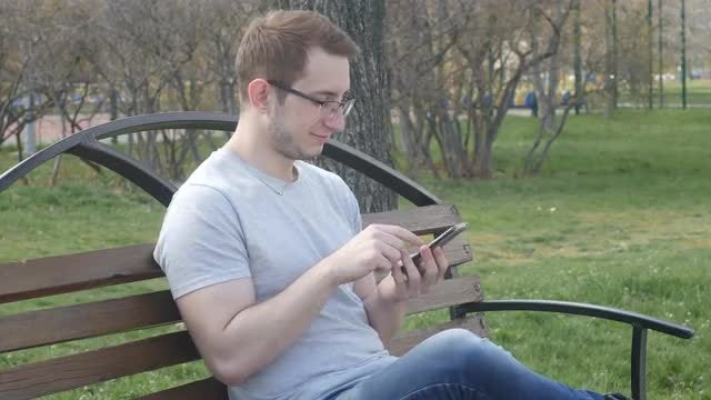 Guy Using Smartphone In Park: Stock Video