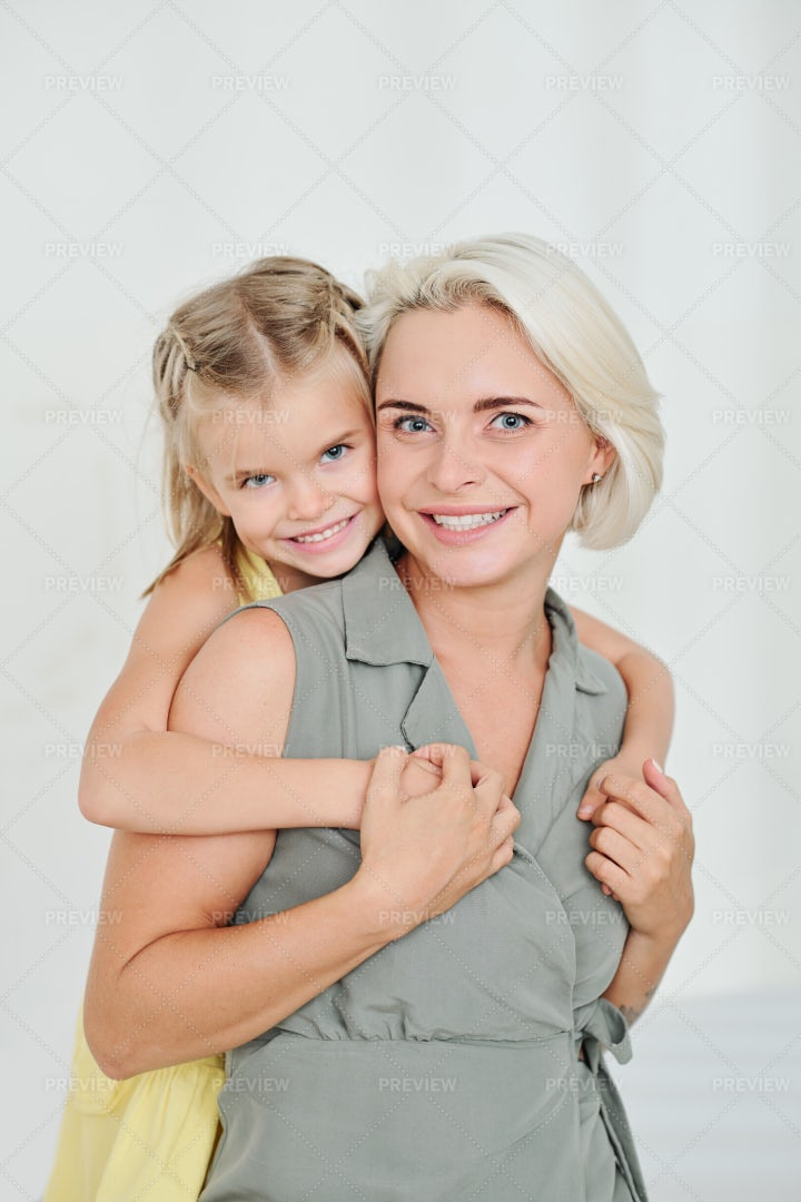 Girl Hugging Her Mom From Behind: Stock Photos