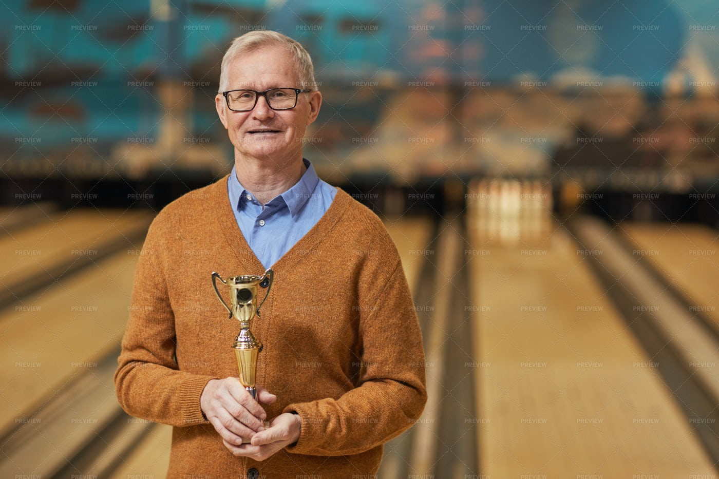 Senior Bowling Player Holding Trophy: Stock Photos