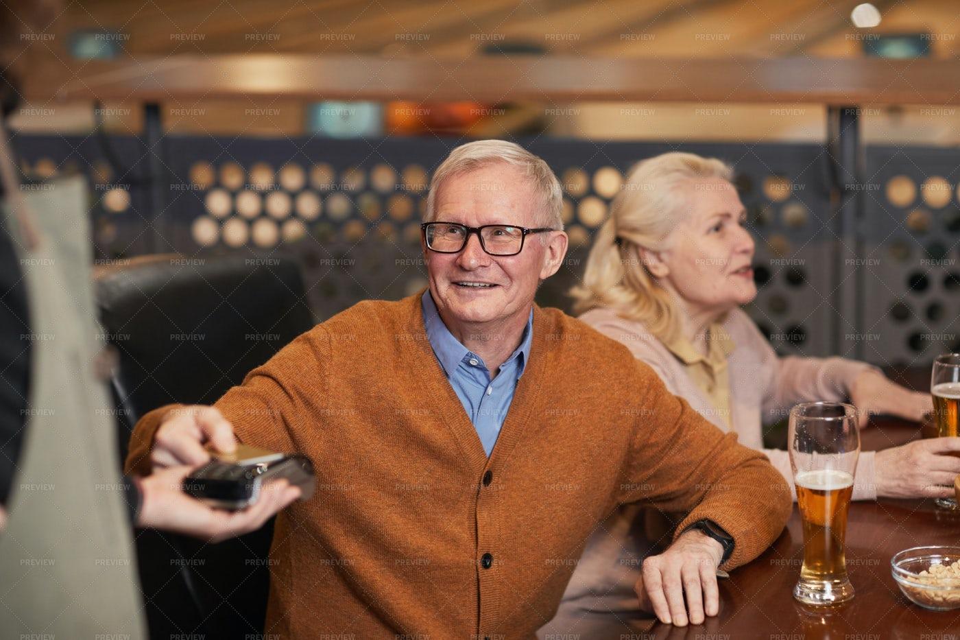Senior Man Paying In Bar: Stock Photos