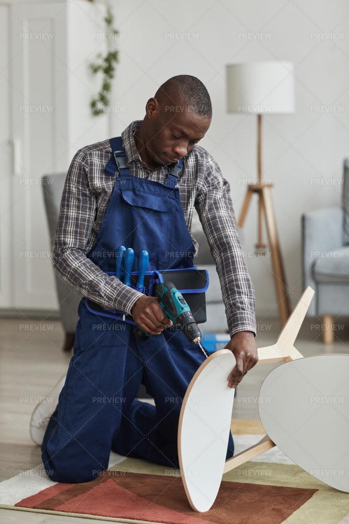 Man In Coveralls Repairing Furniture: Stock Photos