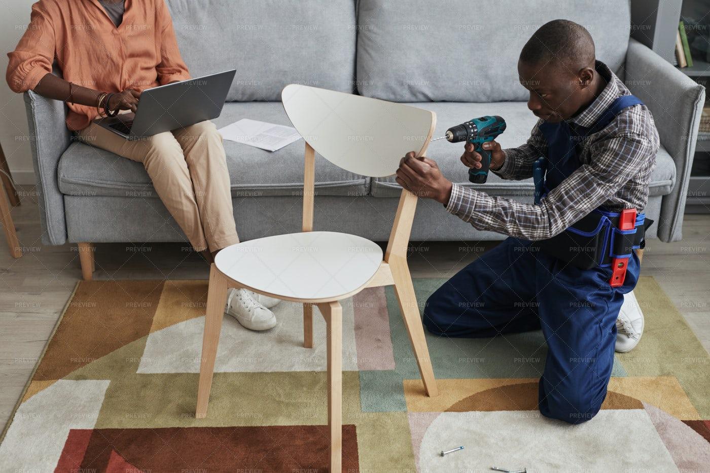 Handyman Assembling A Chair: Stock Photos