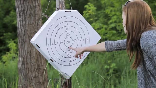 Girl Examines Shooting Target: Stock Video