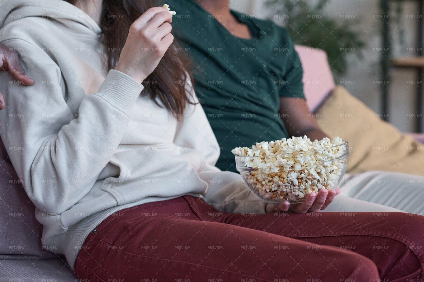 Couple Eating Popcorn Sitting On Sofa: Stock Photos