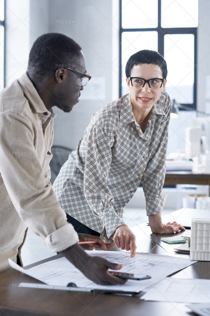 Architect Discussing Work With Colleague: Stock Photos