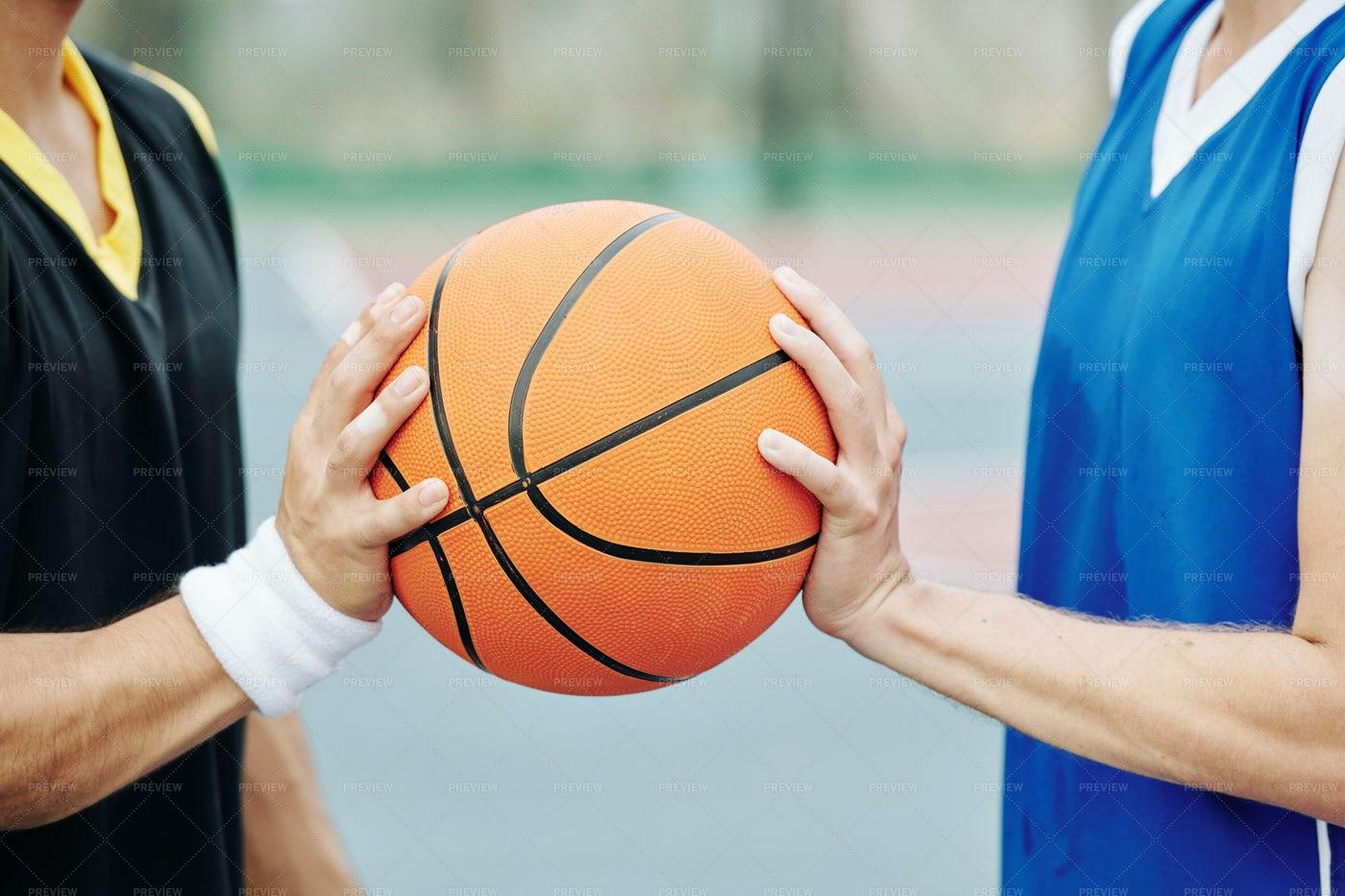 Basketball Players Holding Ball: Stock Photos