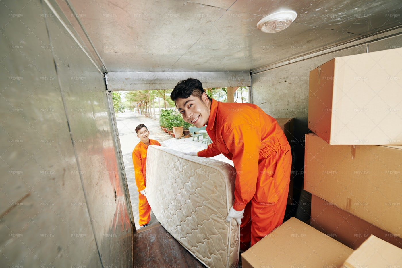 Workers Loading Mattress In Truck: Stock Photos