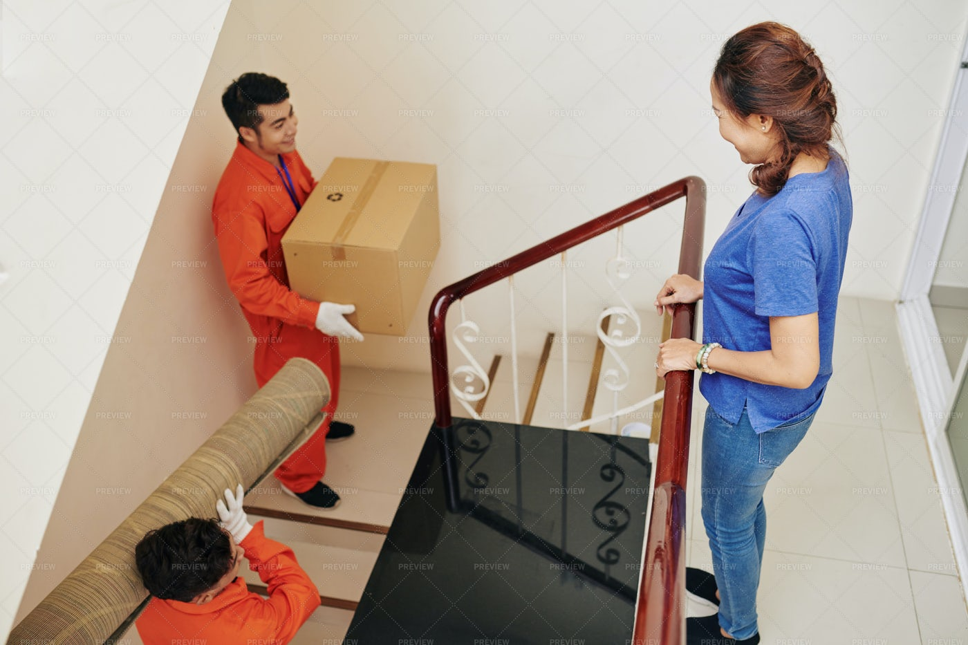 Movers Carrying Stuff In New Apartment: Stock Photos