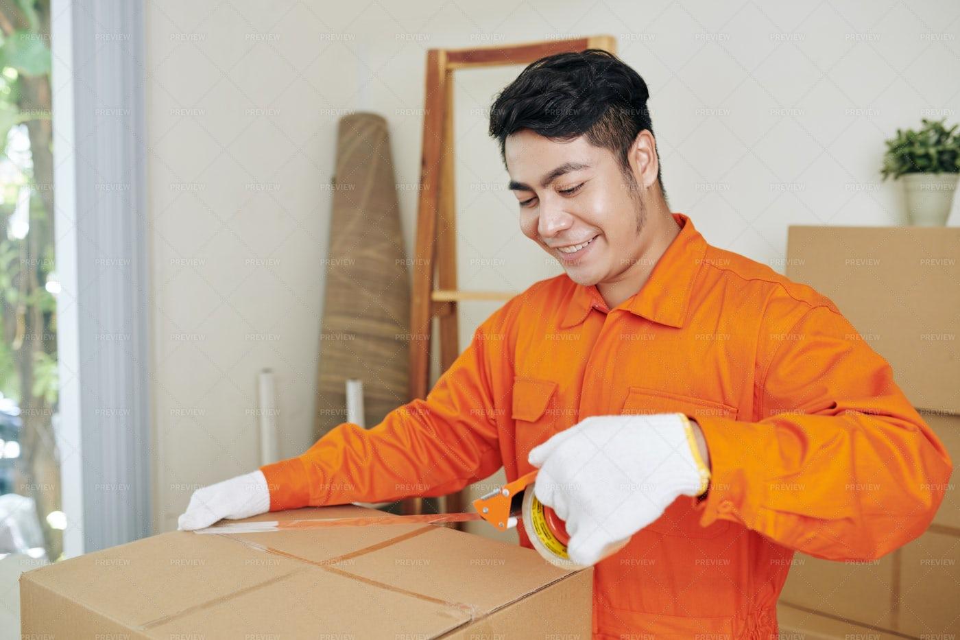 Smiling Worker Sealing Boxes: Stock Photos