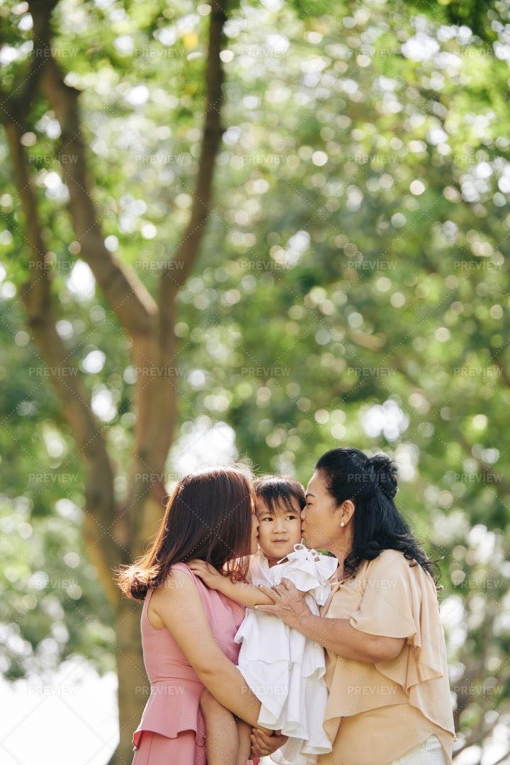 Mother And Grandmother Kiss A Girl: Stock Photos