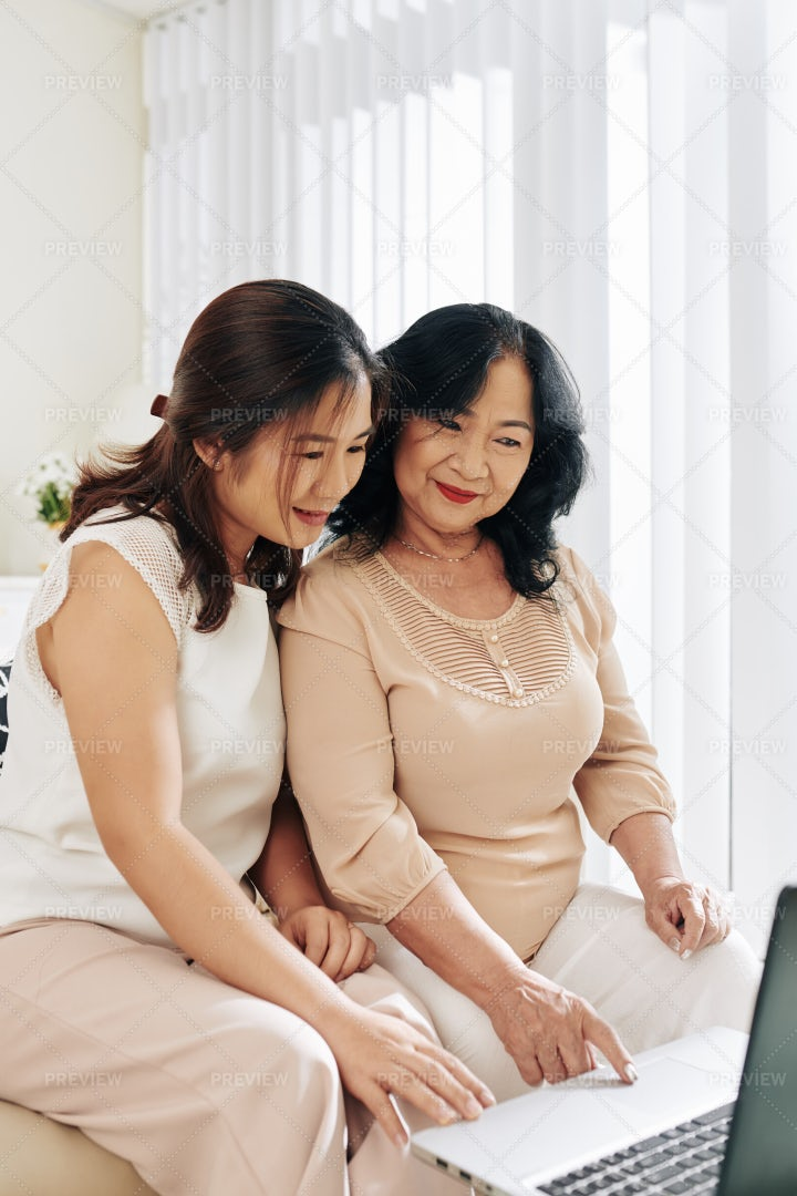 Woman Teaching Her Mom How To Use Laptop: Stock Photos