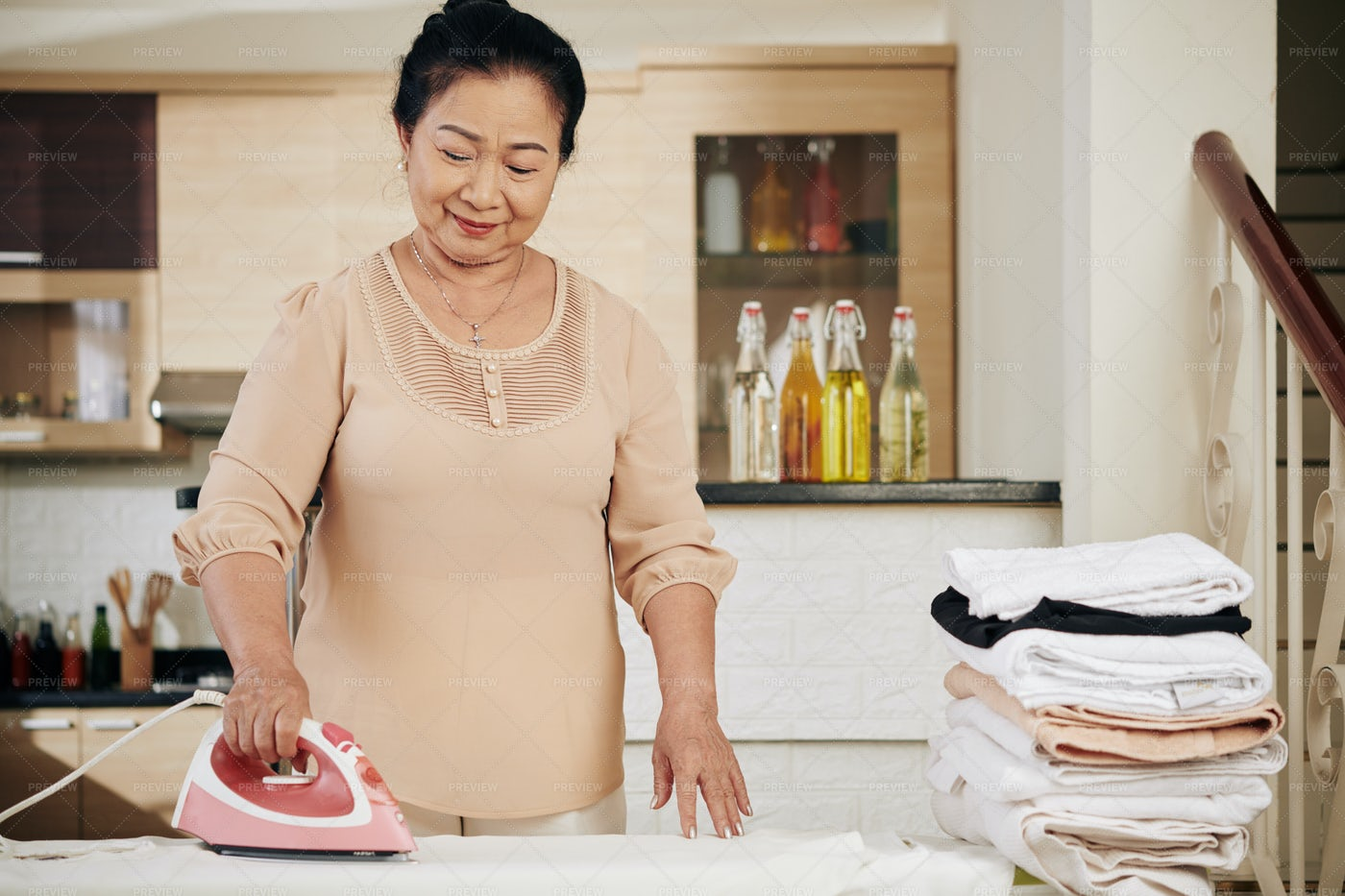 Senior Woman Ironing Towels: Stock Photos
