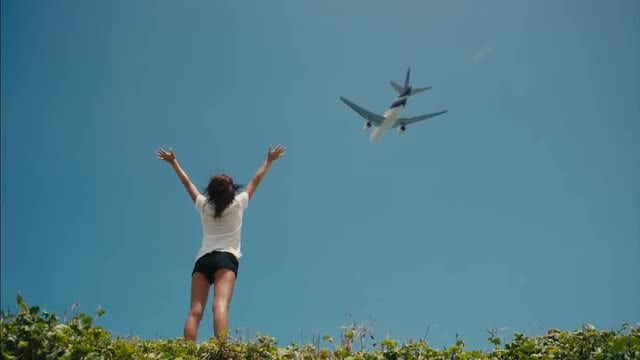 Plane Passes Over Waving Woman: Stock Video