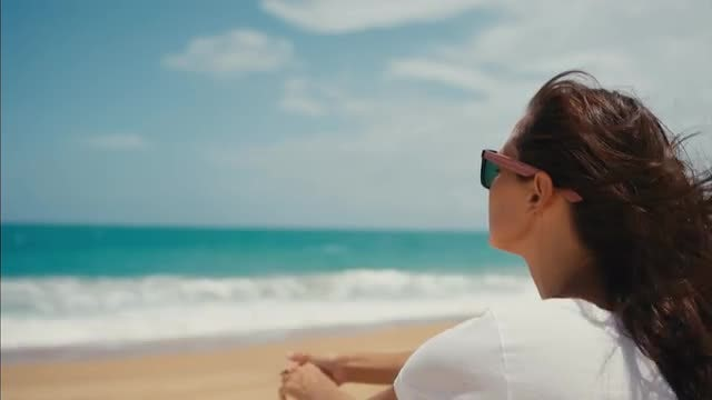 Woman sitting On The Beach: Stock Video