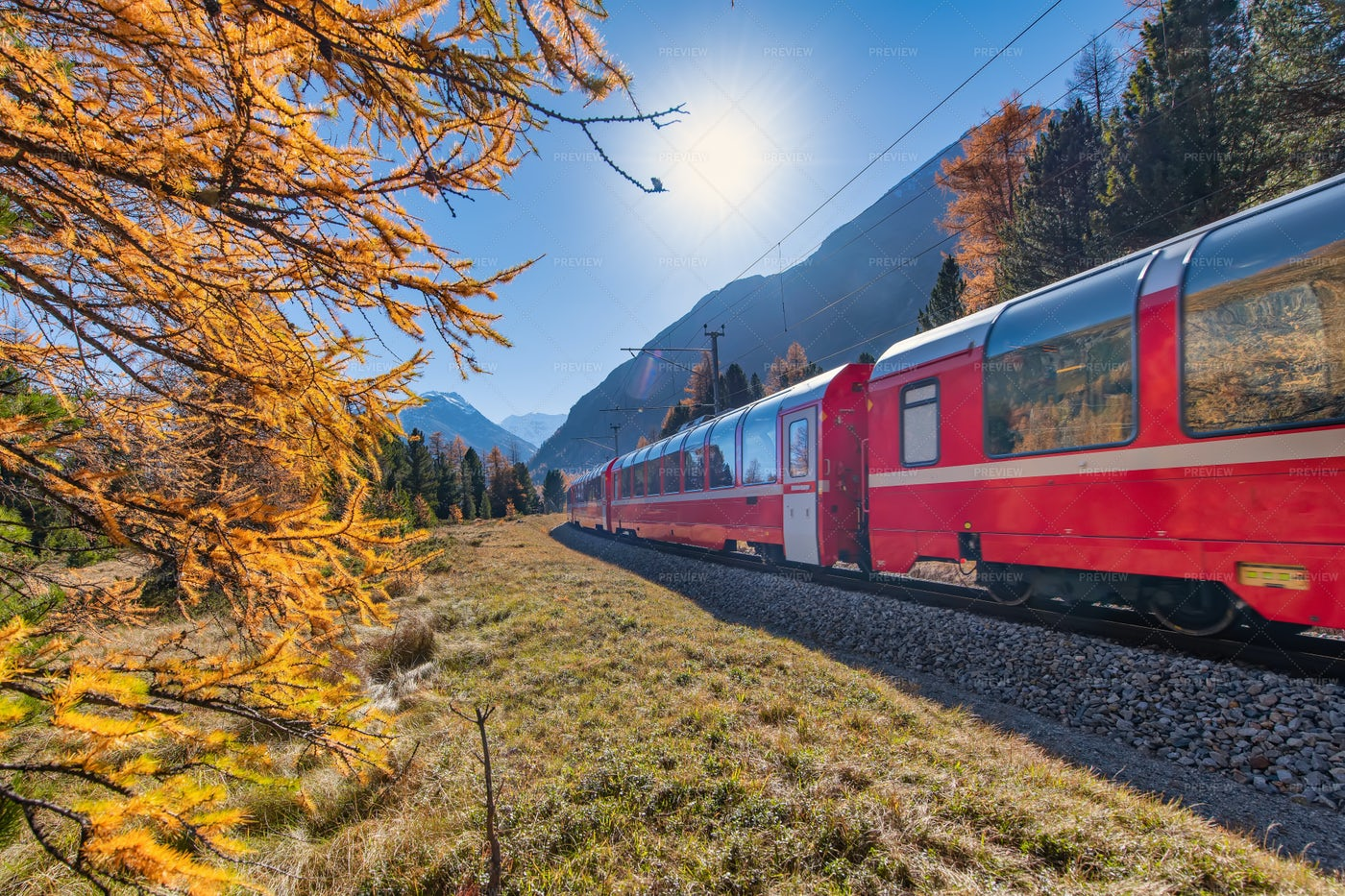 Red Train Crossing The Alps: Stock Photos