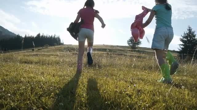 Kids Running On Wet Grass: Stock Video