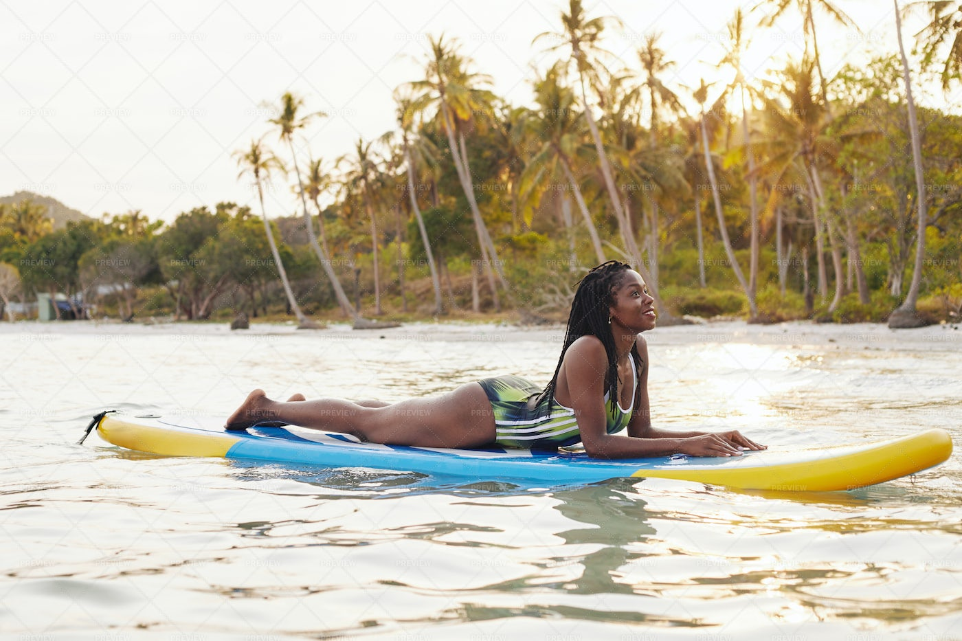 Woman Lying On Surfboard At The Sea: Stock Photos