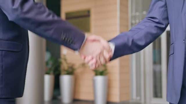 Two Businessmen Exchanging A Handshake : Stock Video