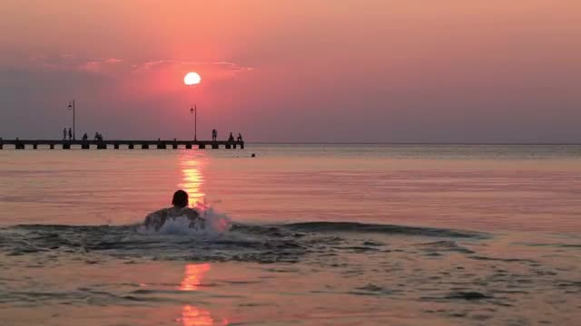 Man Swimming During Sunset: Stock Video