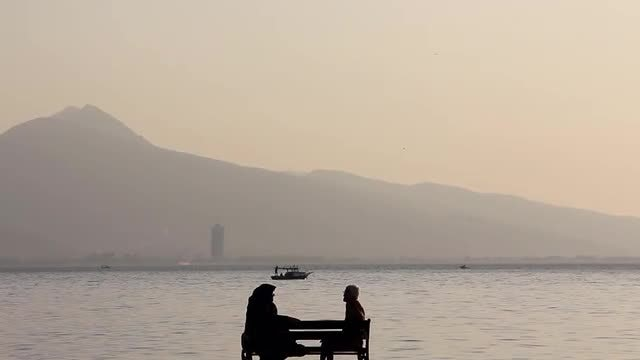 Old Women Sitting By Beach: Stock Video