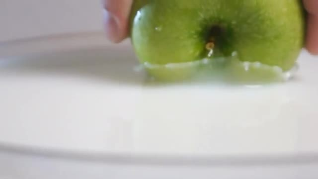 Inserting Green Apple In Milk: Stock Video