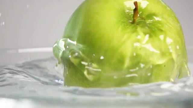 Green Apple Falling In Water: Stock Video