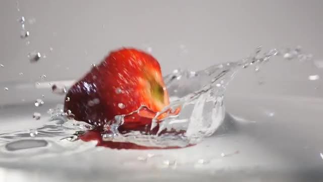 Three Strawberries Plunge Into Water: Stock Video