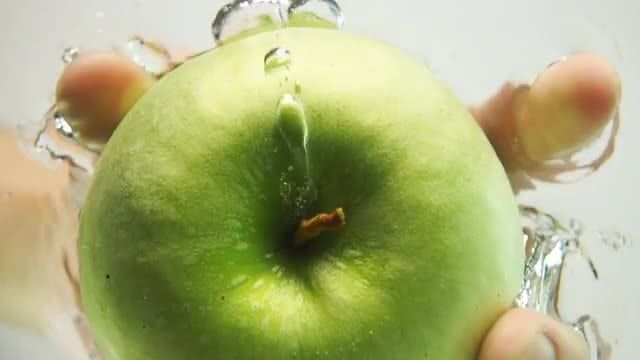 Pushing An Apple Into Water: Stock Video