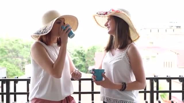 Two Women Drinking Coffee Outdoors: Stock Video