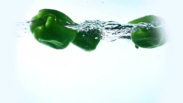 Green Peppers Floating In Water: Stock Video