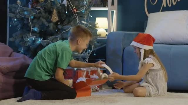 Kids Unwrapping Christmas Gifts: Stock Video