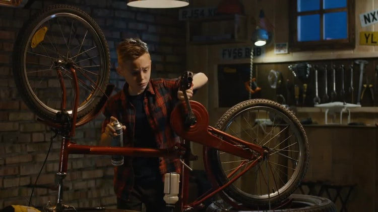 Boy Repairing A Bicycle: Stock Video