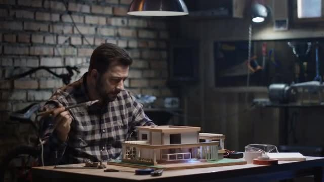 Man Repairs Model House: Stock Video