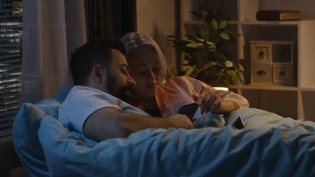 Couple Using Phone In Bed: Stock Video